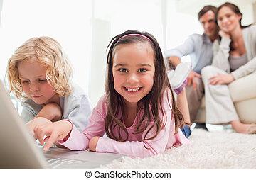 irmãs, usando, um, laptop, enquanto, seu, pais, é, em, a, fundo, em, um, sala de estar