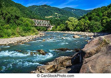 Iron and stone on mountain river - Iron Bridge and a giant...