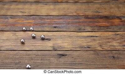 Iron balls rolling randomly along a vintage wooden table....