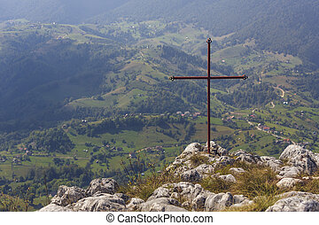 Iron cross above valley - Red iron cross on top of a rock,...