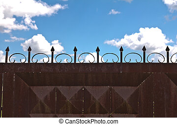 iron fence and a blue sky with clouds