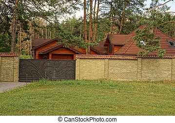 iron gate and brown brick fence outside in green grass