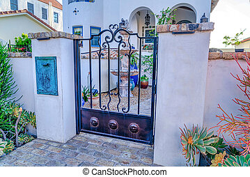 Iron gate and white fence against house with fountain in San Diego California