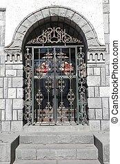 iron gate under stone archway