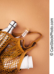 Iron, glass and eco bottles in a string bag on a brown ...