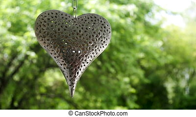 iron heart hanging on a chain on a background of green trees
