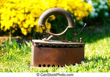 Iron in garden. ancient style, flower blurred background.