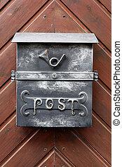 Iron mailbox on a wooden door