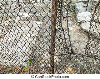 Iron mesh, concrete block on the ground. Yard in the town house