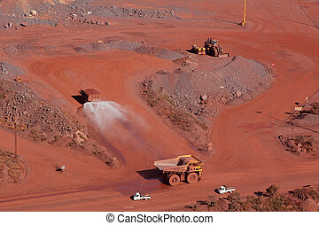Iron ore mining - Large, open-pit iron ore mine with trucks...
