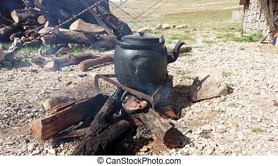 Iron Teapot Sits on Open Fire Heating Water.