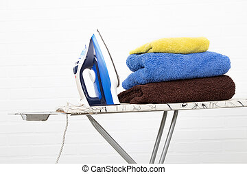 iron with clothes on the ironing board