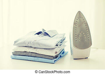close up of iron and clothes on table at home - ironing, ...