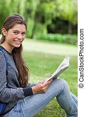 irradiando, direito, olhando jovem, enquanto, câmera, adulto, livro leitura, feliz
