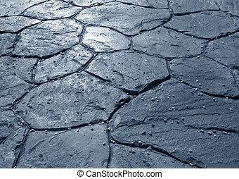 Concrete floor finishing with irregular tiles imitating stone.