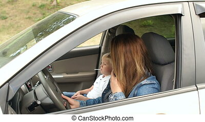 Woman yells at a child in a car while talking on phone.