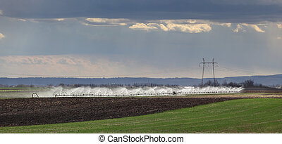 Irrigation equipment watering field in spring