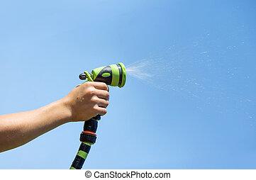Irrigation - Hand holding water sprinkler against blue sky,...