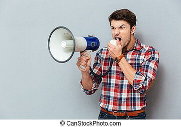 Irritated angry young man in plaid shirt shouting with...