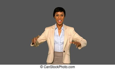 Irritated businesswoman gesturing on grey background