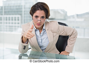 Irritated businesswoman looking at camera in bright office