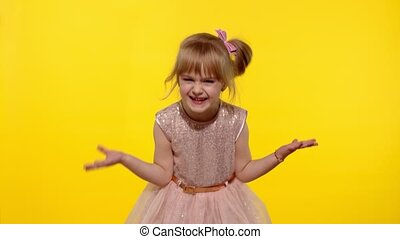 Irritated child girl in dress raising hands in questioning gesture why, what. Kid scolding with indignant expression, blaming in defeat. Yellow background studio. People emotions concept. Copy space