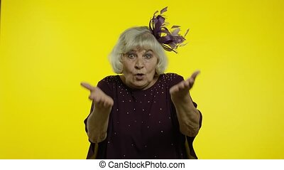 Confused irritated senior old woman raising hands, indignantly asking reason of failure, misunderstanding concept. Elderly stylish lady grandma asking what, why on yellow background. 6k slow motion