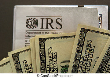 hundred dollar bills fanned out over an IRS envelope, metaphor for paying taxes or getting a refund