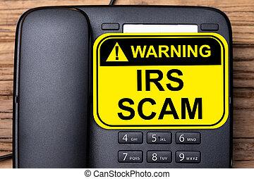 IRS Scam Warning Sign On Landline Phone