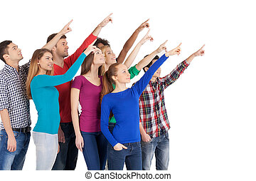 Is it a plane? Group of cheerful young multi-ethnic people standing close to each other and pointing away while standing isolated on white