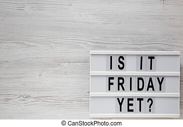 'Is it friday yet?' words on a lightbox on a white wooden background, top view. Overhead, from above, flat lay. Copy space.