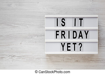 'Is it friday yet ?' words on a lightbox on a white wooden background, top view. Overhead, from above, flat lay. Copy space.