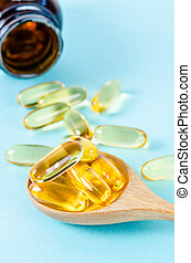 ish oil capsules in wooden spoon with bottle.