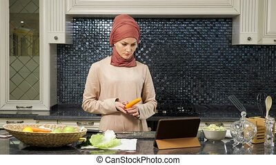 islam woman takes carrot to cut watching halal dish recipe...