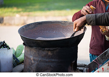 Islamabad, Islamabad Capital Territory, Pakistan - February 2, 2020, A Young boy is roasting fresh corn for the customers.
