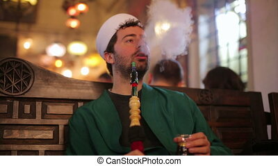 islamic man with traditional dress smoking shisha, drinking...