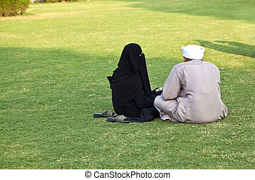 islamic woman in burka sitting on the green with her husband...