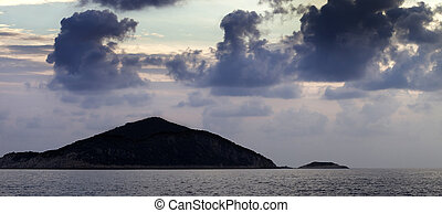 Island in sea and sky with dark clouds at sunset
