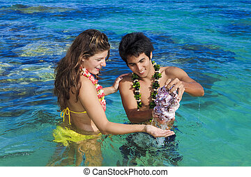 man shows seashells to a young woman