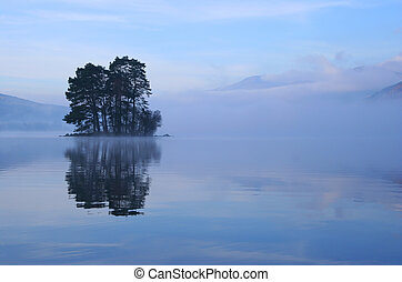 Small tree-covered island rises out of the mist on Loch Tay, Perthshire, Scotland