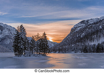 Island with trees in winter frozen lake Predil and sunset -...