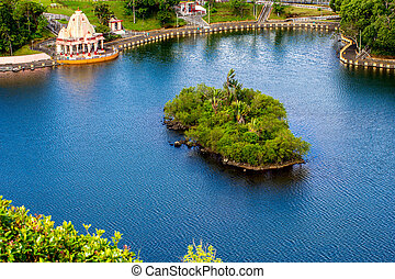 Island with tropical greenery in the blue lake - Island with...