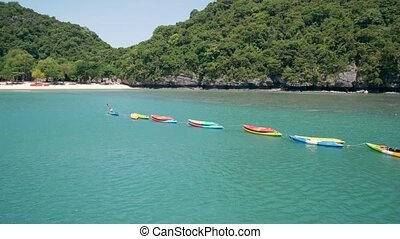 Islands in ocean at Ang Thong National Marine Park near touristic Samui paradise tropical resort. Idyllic turquoise sea natural background with copy space. Kayaks and colorfull sports canoes