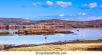 Isle of Skye Landscape - Yacht boat on Loch Dunvegan with mountains, heather covered hills and blue sky in the background
