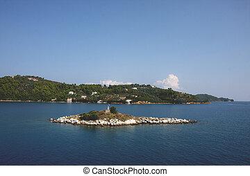 Small island close to Greek island Skiathos at Mediterranean sea