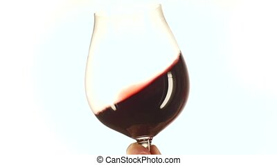 Isolated and moving red wine glass, white, slowmotion, closeup