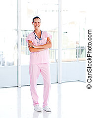 Isolated beautiful nurse standing in front of the camera with folded arms