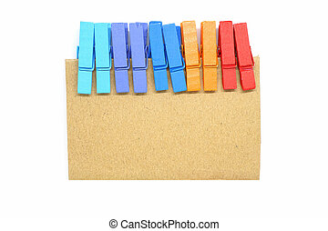 Brown notepad with colorful clip on white background.