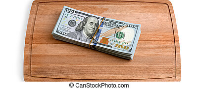 Isolated bundle of dollars. A large stack of hundred-dollar bills sits on a cutting board