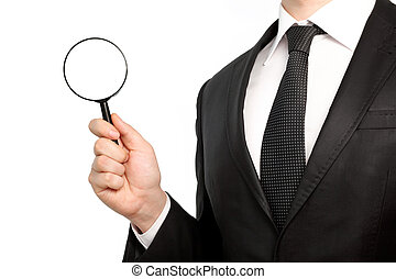 Isolated businessman in a suit holding a magnifying glass